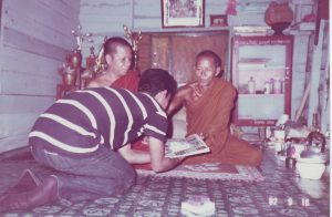 Achan Chanh Ly (left) and Achan Ky (right) receiving offerings from a Lao insurgent at Wat Pa Sanamsai in Ubon Ratchathani Province, Thailand (1982).