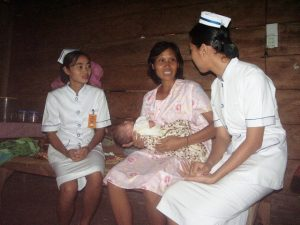 Young midwives consult with a new mother about her infant as part of their clinical training in Java. Photo: Christian Laugen.