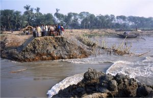 In rural Bangladesh, residents look over a breached embankment.