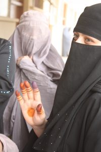 In Helmand province during the 2010 elections, an Afghan woman decorates her hand to hide the ink stain indicating she has voted, which could put her at risk from Taliban retribution (Credit: UK Ministry of Defence).
