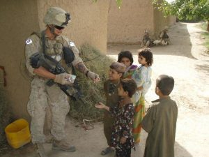 During counter-insurgency operations in Marjah, Afghanistan in 2010, a U.S. Marine hands out candy to the local Afghan children (Credit: Puckett88).