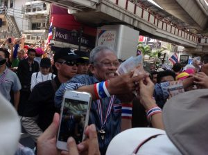 Leader of the protest movement Suthep Theuaksuban is mobbed on the street by well-wishers pressing donations upon him (Credit: Tip Placzek).
