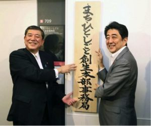 Regional revitalization minister Shigeru Ishiba (left) and Prime Minister Shinzo Abe display a sign in front of Ishiba's new office in Tokyo in September 2014 (Credit: The Japan News).